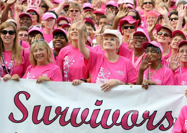 Breast cancer survivors wave as they march into the main stage area during the Susan G., Komen Race for the Cure in St. Louis on June 12, 2010. The race has raised more than $3.3 million for breast cancer research and charities. UPI/BIll Greenblatt