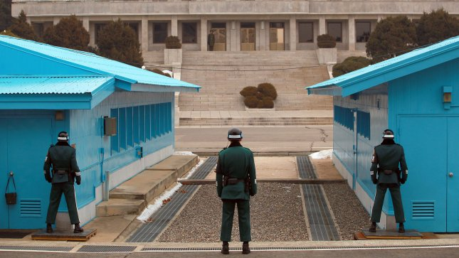South Korean military police stand in an aggressive posture as they watch over the demarcation line (concrete slab connecting the two blue conference halls) separating it from North Korea (background) in the Demilitarized Zone's (DMZ) Joint Security Area (JSA) in Seoul on January 29, 2013. UPI/Stephen Shaver