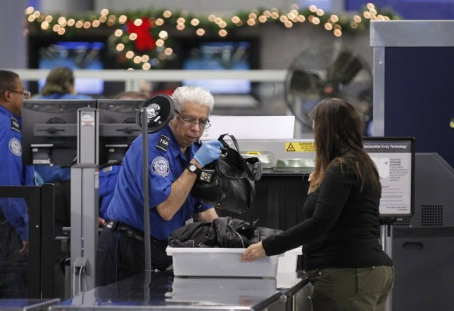 A TSA screener helps a passenger at a security checkpoint at O'Hare International Airport on November 24, 2010 in Chicago. Security ran smoothly on the day before Thanksgiving despite rumors of mass protests of security procedures. UPI/Brian Kersey