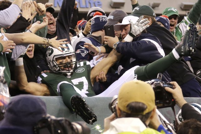 New York Jets' Eric Decker leaps into the seats and celebrates with the fans after catching a 6 yard game-winning touchdown pass in overtime against the New England Patriots at MetLife Stadium in East Rutherford, New Jersey on December 27, 2015. The Jets defeated the Patriots 26-20. Photo by John Angelillo/UPI