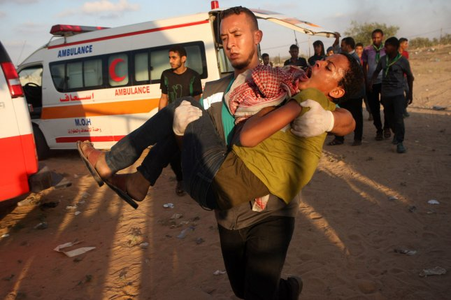 A Palestinian man carries a wounded man away during of clashes with Israeli forces during weekly protest demanding the right to return to their homeland, at the Israel-Gaza border, in the southern Gaza east Rafah on Friday. Photo by Ismael Mohamad/UPI