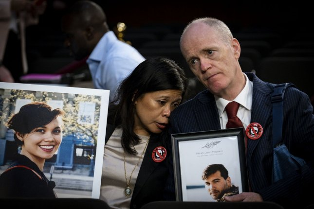 Relatives hold photographs of loved ones killed in crashes involving the Boeing 737 Max, during a hearing on Capitol Hill in Washington, D.C., on October 29, 2019. File Photo by Pete Marovich/UPI