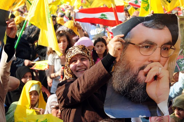 Lebanese Moslem Shiite women carry posters of Hezbollah leader Hassan Nasrallah in Beirut's southern suburbs. (UPI Photo)