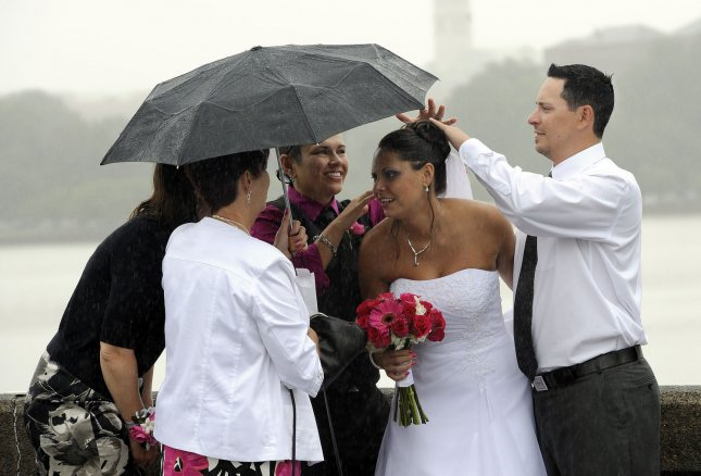 Erin Kleintop (RC) and Amy Vagnoni (LC) are photographed in the rain after their wedding in Washington, DC, on September 9, 2011. UPI/Roger L. Wollenberg