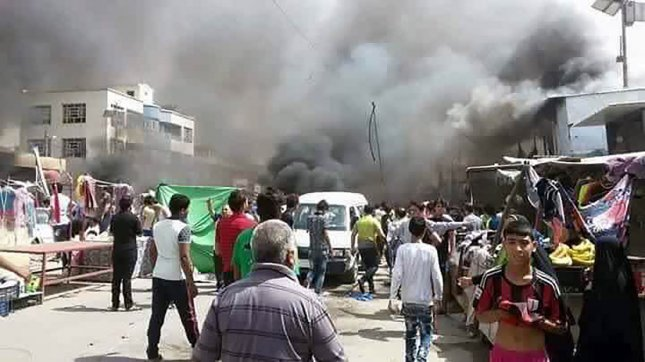 Iraqi firefighters extinguish a fire as civilians gather after a car bomb at a commercial area in Karada neighborhood, Baghdad, Iraq, on July 3, 2016. in Karrada central Baghdad's in Iraq. The blast killed at least 165 people and also wounded more than 225 people, security and medical officials said. The Islamic State group issued a statement claiming the suicide car bombing. photo by Methak A lShamaree /UPI