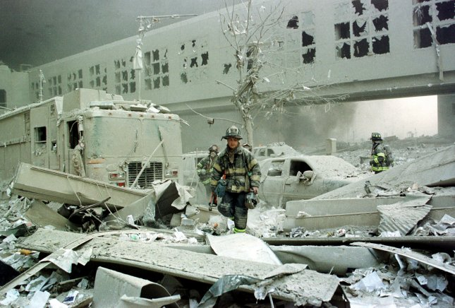 Firefighters walk among the rubble in front of the World Trade Center 1 building following a terrorist attack involving two planes flying into the World Trade Center buildings on September 11, 2001 in New York City. File Photo by Monika Graff/UPI