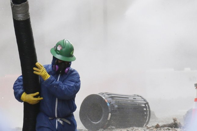 A worker wears a mask to clean the streets of dust and asbestos in New York City after a steam pipe explosion in 2018. Asbestos can cause a number of lung diseases, including cancer. File Photo by John Angelillo/UPI
