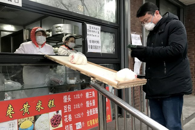 A famous Chinese dumpling shop passes orders to waiting customers over a small, makeshift bridge due to the threat of spreading the deadly coronavirus in Beijing on Monday. Photo by Stephen Shaver/UPI