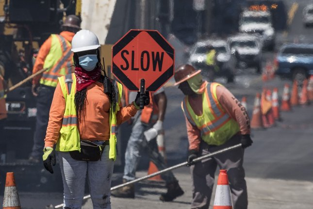 Masked construction workers are seen paving 16th Street in downtown San Francisco, Calif. File Photo by Terry Schmitt/UPI