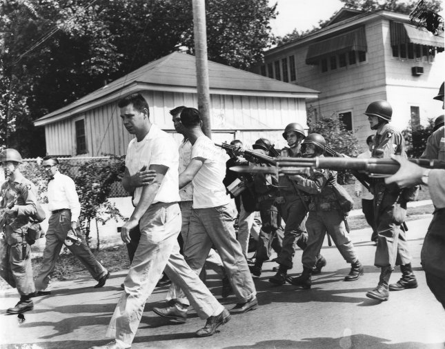 Original caption: Three men from the mob around little Rock Central high School are driven from the area at bayonet point by these soldiers of the 101st Airborne Division on September 25, 1957. The presence of the troops permitted the nine Negro students to enter the school with only minor background incidents. President Eisenhower was compelled to enforce the Supreme Court's public school desegregation decision with troops after the integrity of the court was challenged by Arkansas Governor Orval Faubus. File photo UPI