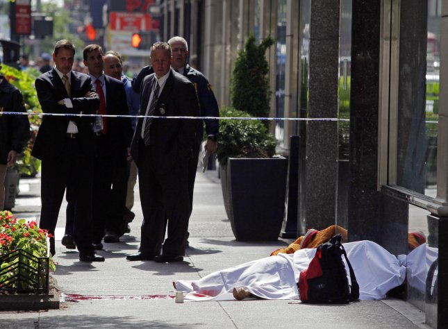 Police investigate around the body of a dead victim from a shooting on 33rd Street outside of the Empire State Building in New York City on August 24, 2012. The gunman, Jeffrey Johnson, 53 was laid off about a year ago and went to his former workplace Friday morning and shot a co-worker in the face, killing him, before a shootout broke out between him and New York police officers near the Empire State Building. A total of nine people were injured. UPI/John Angelillo