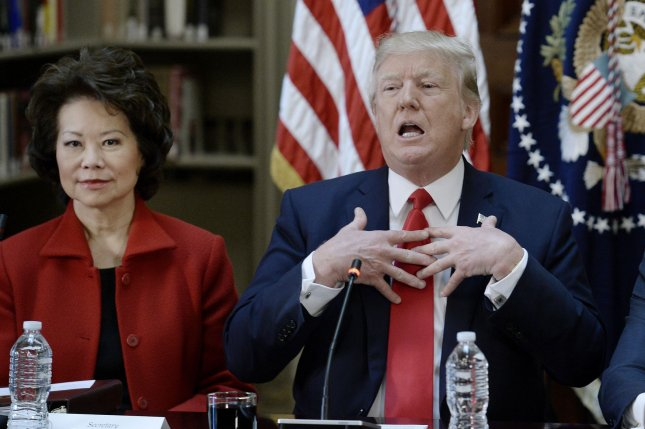 President Donald Trump speaks as Secretary of Transportation Elaine Chao looks on during a policy meeting in April. Chao said Trump's plan to update transportation infrastructure will include wage protections for workers sought by Democrats on Capitol Hill. Pool photo by Olivier Douliery/UPI