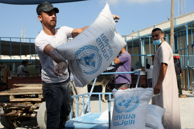 Palestinian refugees receive aid distributed by UNRWA amid the COVID-19 coronavirus disease outbreak, at the United Nations centre in Rafah on October 14. U.S. Secretary of State Antony Blinken announced new U.S. aid for the UNRWA on Wednesday. File Photo by Ismael Mohamad/UPI