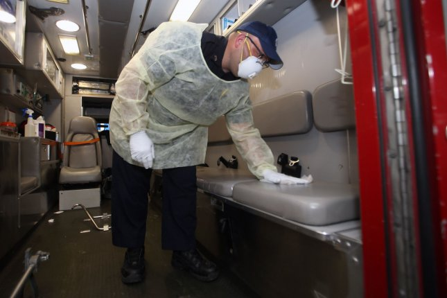 St. Louis Fire Department paramedic Andrew Beasley wears a mask, gloves and a gown as he disinfects the back of an ambulance with a bleach mix, after delivering a patient to the Emergency Department at Barnes-Jewish Hospital in St. Louis on March 16.  Photo by Bill Greenblatt/UPI