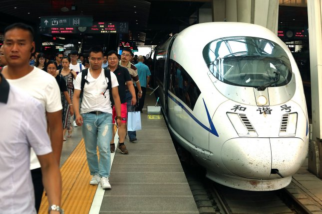 Commuters walk near a high-speed train after arriving in Beijing. According to a survey by Ipsos Public Affairs, China was ranked as the most optimistic country in the world. Photo by Stephen Shaver/UPI