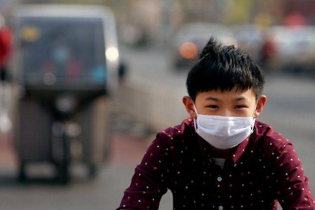 People continue wearing protective face masks on empty streets despite reports of a decline in the threat of the COVID-19 virus in Beijing on Monday. Photo by Stephen Shaver/UPI