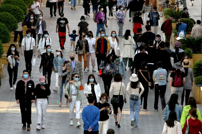 Pedestrians no longer practice social distancing but continue to wear protective face masks while visiting a popular entertainment area in Beijing on April 26, 2020. Photo by Stephen Shaver/UPI
