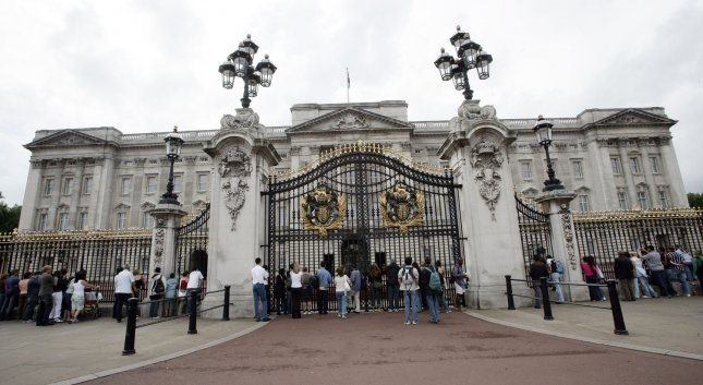 Tourists look through the gates at the queen's residence, Buckingham Palace, in London, one week after the terrorist threat was raised to critical on August 17, 2006. The palace will be getting a $458 million renovation beginning in April 2017. Some of the wiring and pipes in the palace have not been replaced in 60 years. Photo by Hugo Philpott/UPI
