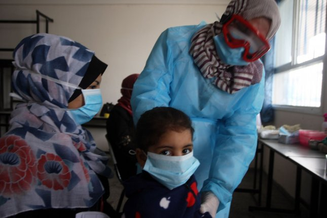 A Palestinian doctor wearing a protective facemask checks the temperature of a child at a United Nations Relief and Works Agency for Palestinian Refugees' school at the Khan Younis Camp for refugees in southern Gaza on March 18. Photo by Ismael Mohamad/UPI