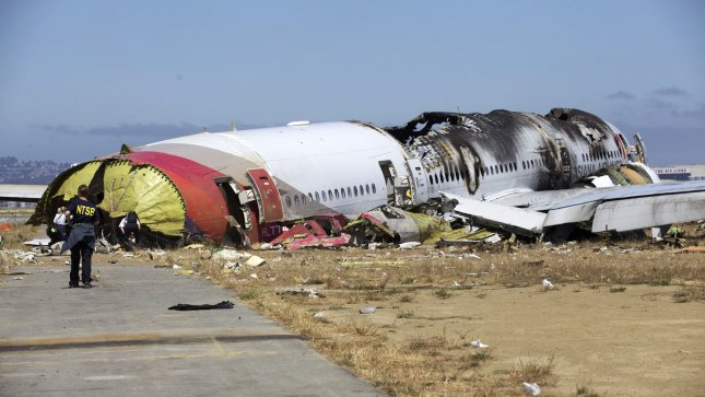 In this photo provided by the National Transportation Safety Board, NTSB investigators inspect the scene of the crash of Asiana Flight 214 in San Francisco, California on July 7, 2013. The Boeing 777 was en route from Shanghai with a layover in Seoul, South Korea, carrying 291 passengers. Two people died and more than 180 were injured. Pilot Lee Kang-kook had logged more than 9,000 hours on various aircraft, but only 43 hours on the Boeing 777 and was considered still in training on that aircraft. UPI.