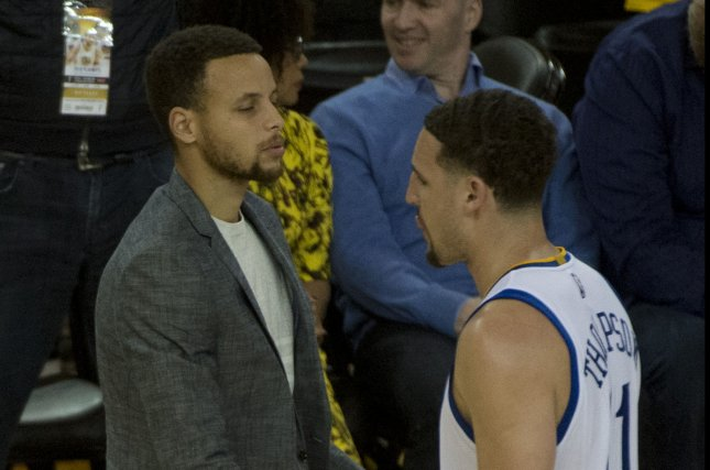 Golden State Warriors' Stephen Curry shakes Klay Thompson's hand. Photo by Terry Schmitt/UPI