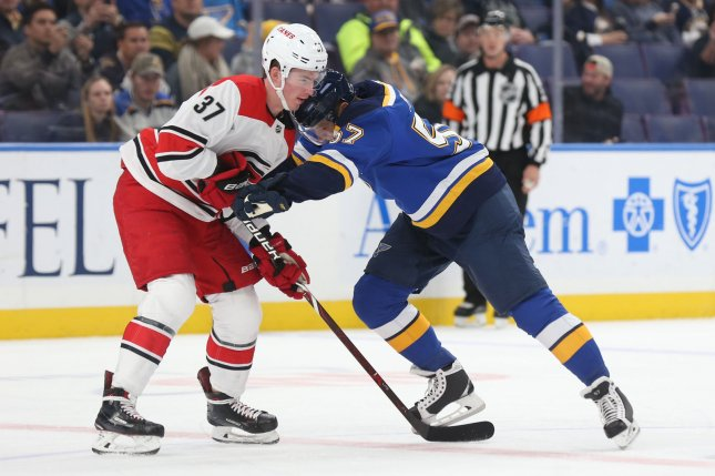 St. Louis Blues' David Perron pushes Carolina Hurricanes' Andrei Svechnikov of Russia, away from him as the two wait for a face off in the first period on November 6 at the Enterprise Center in St. Louis. Photo by Bill Greenblatt/UPI