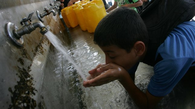 Children drink water at a water purification station on October 27, 2009. UPI/Ismael Mohamad