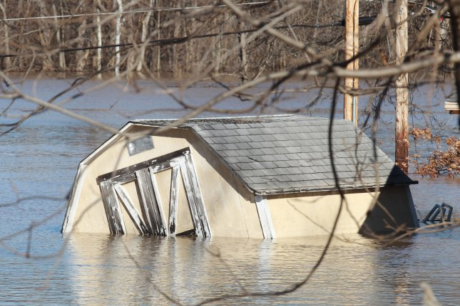 A shed sits wedged against a power pole along the Meramec River as flood waters begin to recede in Arnold, Missouri on January 1, 2016. Flooding statewide from three straight days of rain caused evacuations, road closures and fifteen deaths. Photo by Bill Greenblatt/UPI