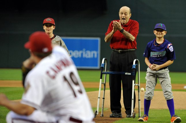Hall of Fame broadcaster Joe Garagiola (C) applauds first pitch participants before the Arizona Diamondbacks-San Francisco Giants game on opening day of Major League Baseball at Chase Field in Phoenix, Arizona on March 31, 2014. File photo by Art Foxall/UPI