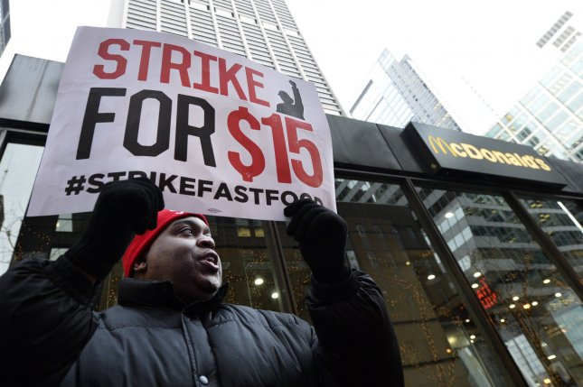 An activist calls for raising the minimum hourly wage to $15 in Chicago. File Photo by Brian Kersey/UPI