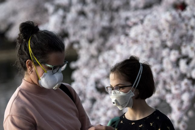 A family wears masks as they visit the blooming cherry blossoms in Washington D.C. in March. File Photo by Kevin Dietsch/UPI