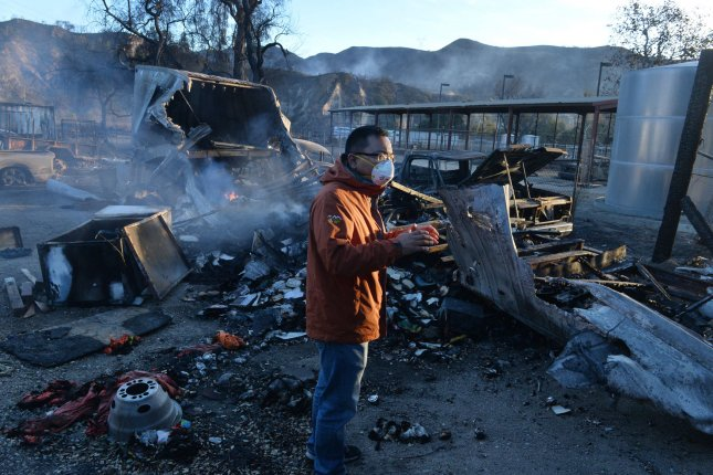 A reporter form Chinese Central Television does a standup among fire debris in Tujunga, California on December 7, 2017. Conditions worsened in Southern California as four major wildfires burned with little containment, prompting 160,00 people to flee. Photo by Jim Ruymen/UPI