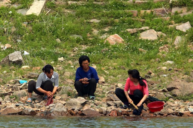 North Korean women wash clothing on the banks of the Yalu River near Sinuiju, across the Yalu River from Dandong, China's largest border city with North Korea. In another border area facing China, North Korea plans to destroy 300 family homes, according to a source in the country. File Photo by Stephen Shaver
