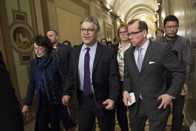 Sen. Al Franken (C), D-Minn., joined by his wife Franni (L), walks to the Senate Chambers to deliver his resignation speech, at the U.S. Capitol on Thursday. Franken is resigning in the wake of several sexual misconduct allegations, some of which he is denying. Photo by Kevin Dietsch/UPI