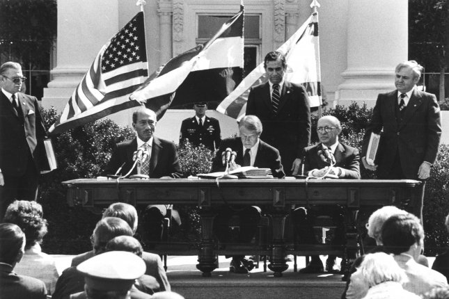Egyptian president Anwar Sadat and Israeli prime minister Menachem Begin sign the Egypt–Israel Peace Treaty in Washington, DC, on March 26, 1979, with United States president Jimmy Carter acting as witness to the proceedings. UPI File Photo