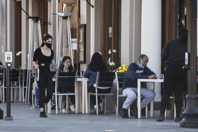 A waitress brings water to patrons seated on the sidewalk outside of Flights Restaurant in Burlingame, Calif., on July 14. California now has the highest number of confirmed cases of COVID-19 since the start of the pandemic. Photo by Terry Schmitt/UPI