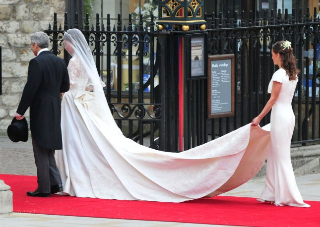 Kate Middleton is escorted into Westminster Abbey for her wedding to Prince William by her father Michael, as her maid of honor Philippa Middleton holds her gown, in London on April 29, 2011. UPI/Kevin Dietsch
