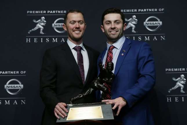 Oklahoma quarterback Baker Mayfield (R) holds the Heisman Trophy with Oklahoma coach Lincoln Riley (L) on December 9, 2017 at the Marriott Marquis in New York City. Photo by John Angelillo/UPI