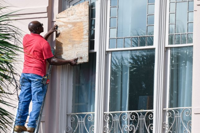 A worker covers windows on a historic home with plywood in preparation for Hurricane Dorian on Monday in Charleston, S.C. Photo by Richard Ellis/UPI