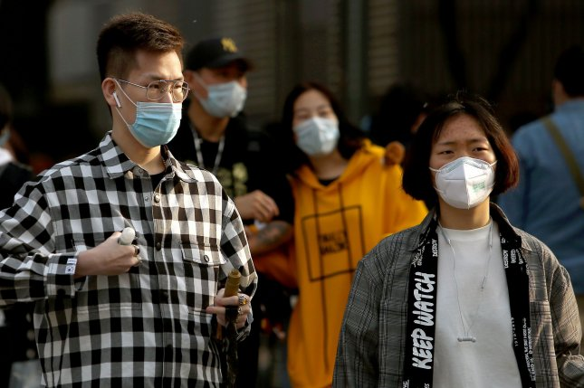 Chinese people continue to wear protective face masks outside in Beijing on Thursday even though the government has declared the threat of the Covid-19 outbreak basically finished. Photo by Stephen Shaver/UPI