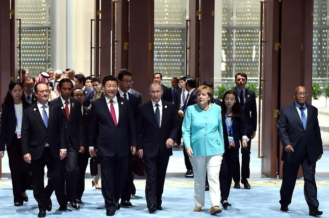 Chinese President Xi Jinping, at center, Russian President Vladimir Putin, to the right of Xi, and German Chancellor Angela Merkel, to the right of Putin, as well as other world leaders head to the opening ceremony of the G20 Summit in Hangzhou, the capital of Zhejiang Province, on September 4, 2016. World leaders have come to China for the start of the G20 Summit, where heads of states will discuss global economics, trade, climate and terrorism issues. Pool Photo by Li Tao/UPI