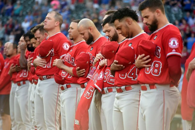 Members of the Los Angeles Angels wear No. 45 on their jerseys and hold Tyler Skaggs' jersey during the national anthem prior to their game against the Texas Rangers Tuesday at Globe Life Park in Arlington, Texas. Photo by Ian Halperin/UPI