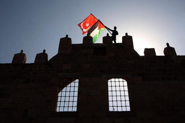A demonstrator holds Palestinian and Turkish flags Monday during a rally to support Turkey's military incursion in northeastern Syria, in Khan Younis,Gaza Strip. Photo by Ismael Mohamad/UPI