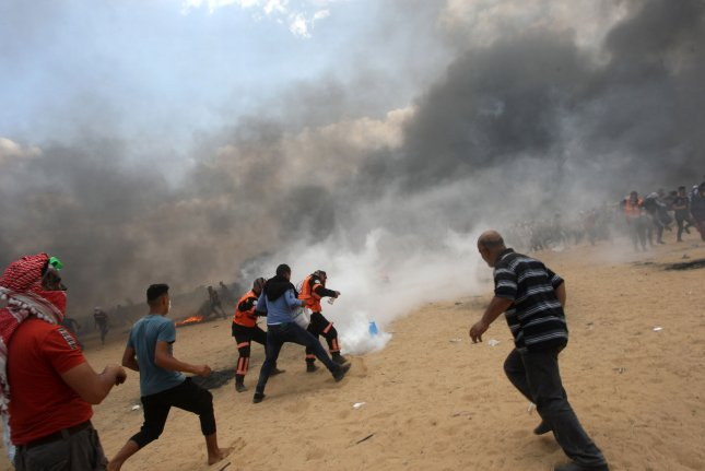 Palestinians run from tear gas fired by Israeli troops during a protest near the Gaza-Israel border in Rafah on May 14. Thursday, a member of a Gaza family was charged with falsely claiming Israeli tear gas killed his 8-month-old niece that day. File Photo by Ismael Mohamad/UPI