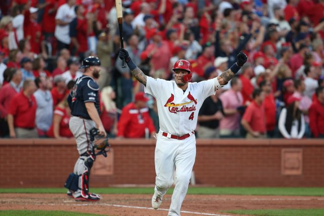 St. Louis Cardinals catcher Yadier Molina raises his arms to the crowd after hitting a sacrifice fly to score the winning run in the 10th inning against the Atlanta Braves in Game 4 of the National League Division Series on Monday at Busch Stadium in St. Louis. Photo by Bill Greenblatt/UPI