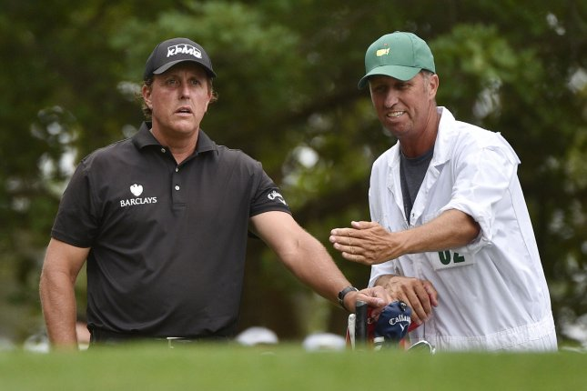 Phil Mickelson and caddie Jim Bones Mackay stand on the 4th hole tee box in the final round of the 2015 Masters Tournament at Augusta National Golf Club in Augusta, Georgia on April 12, 2015. Photo by Kevin Dietsch/UPI