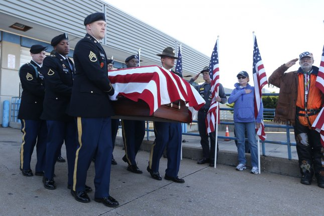 A military honor guard carries the remains of WWII fallen Staff Sgt. Michael Aiello to a hearse after arrival at St. Louis Lambert International Airport in St. Louis on Wednesday. Photo by Bill Greenblatt/UPI
