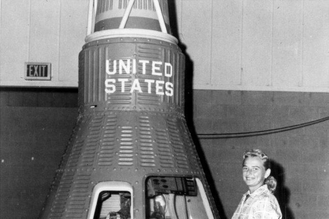 Astronaut trainee Jerrie Cobb stands near a Mercury program space capsule at the Kennedy Space Center in the early 1960s. Photo by NASA/UPI