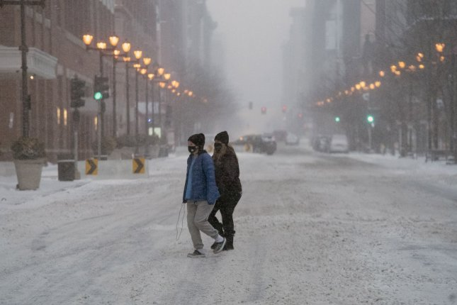 Masked women cross the normally busy Washington Avenue in downtown St. Louis, Mo., during a snowstorm on Monday. Photo by Bill Greenblatt/UPI