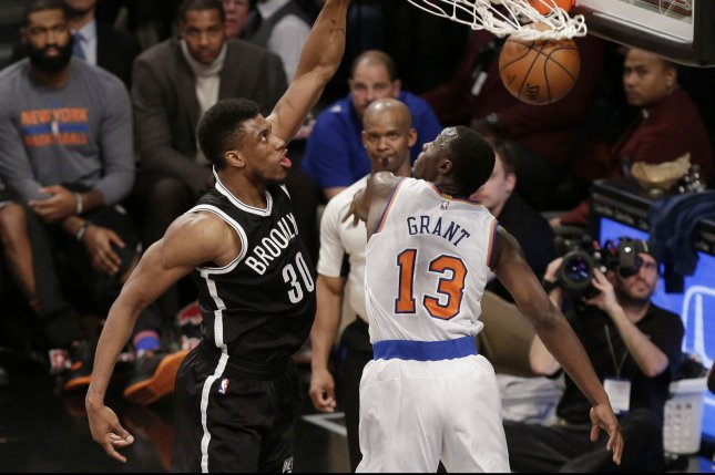 Brooklyn Nets' Thaddeus Young dunks the basketball over New York Knicks' Jerian Grant in the 4th quarter at Barclays Center in New York City on January 13, 2016. The Nets defeated the Knicks 108- 104. Photo by John Angelillo/UPI